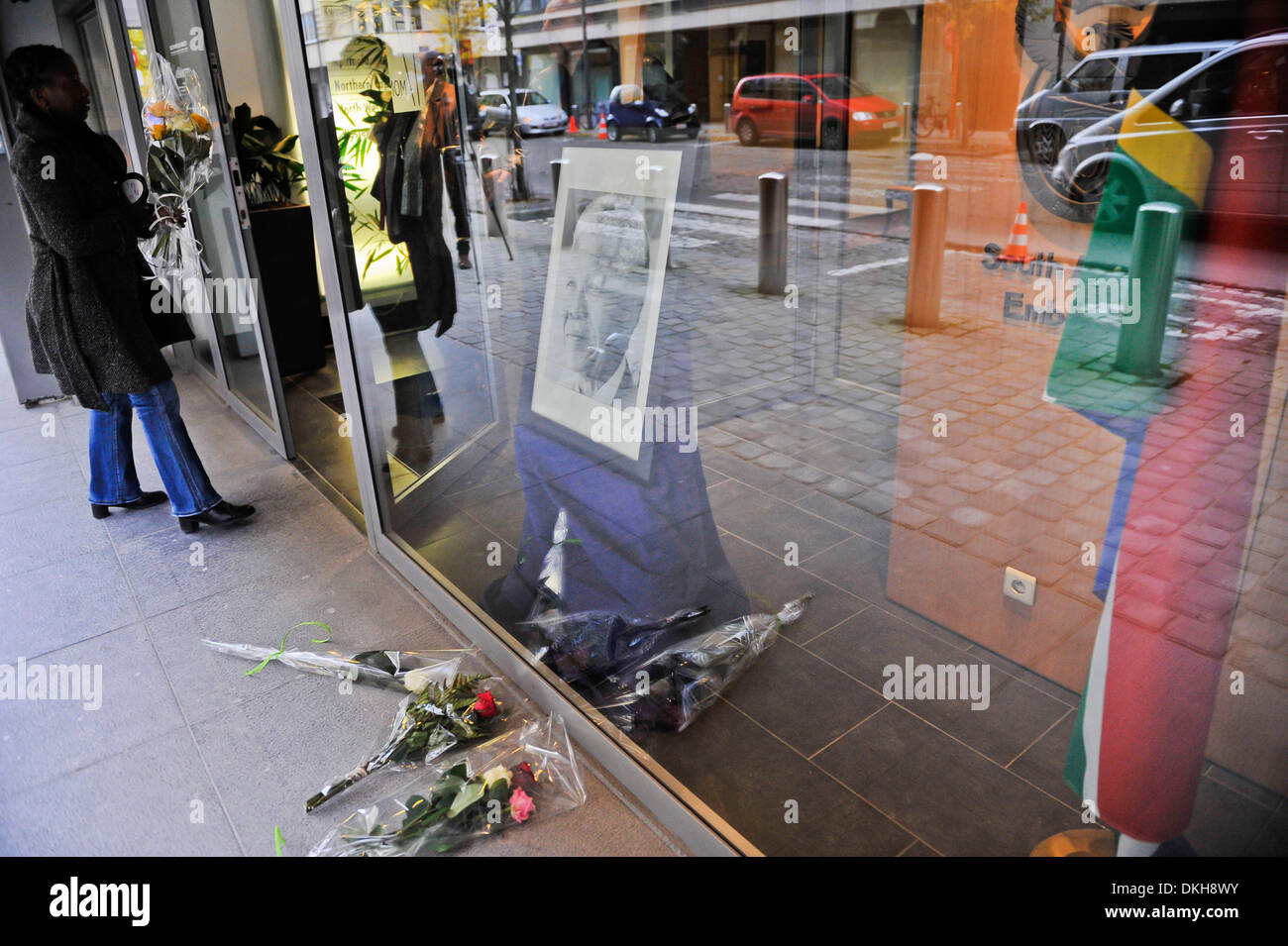 Brussels, Belgium. 6th December 2013. A woman holding a bunch of flowers walks into South African embassy in Brussels, capital of Belgium, Dec 6, 2013. Condolence messages are pouring in for the late former South African president from all over the world on Friday. (Xinhua/Ye Pingfan/Alamy Live News) - Stock Image