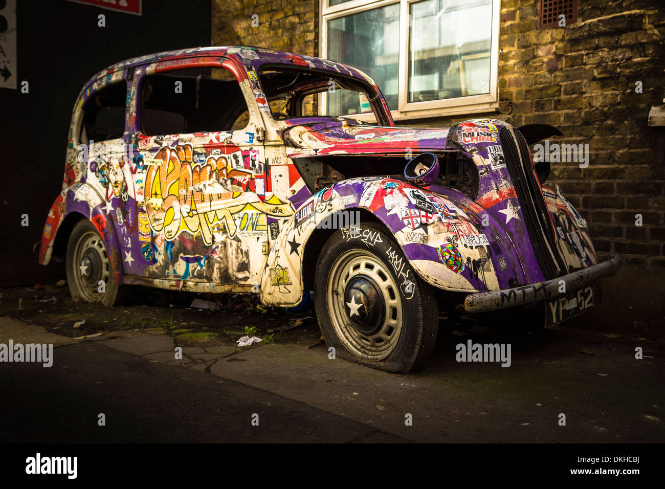 An old abandoned car, covered in graffiti, is a regular attraction for visitors to the Camden Lock Village Market in London. - Stock Image
