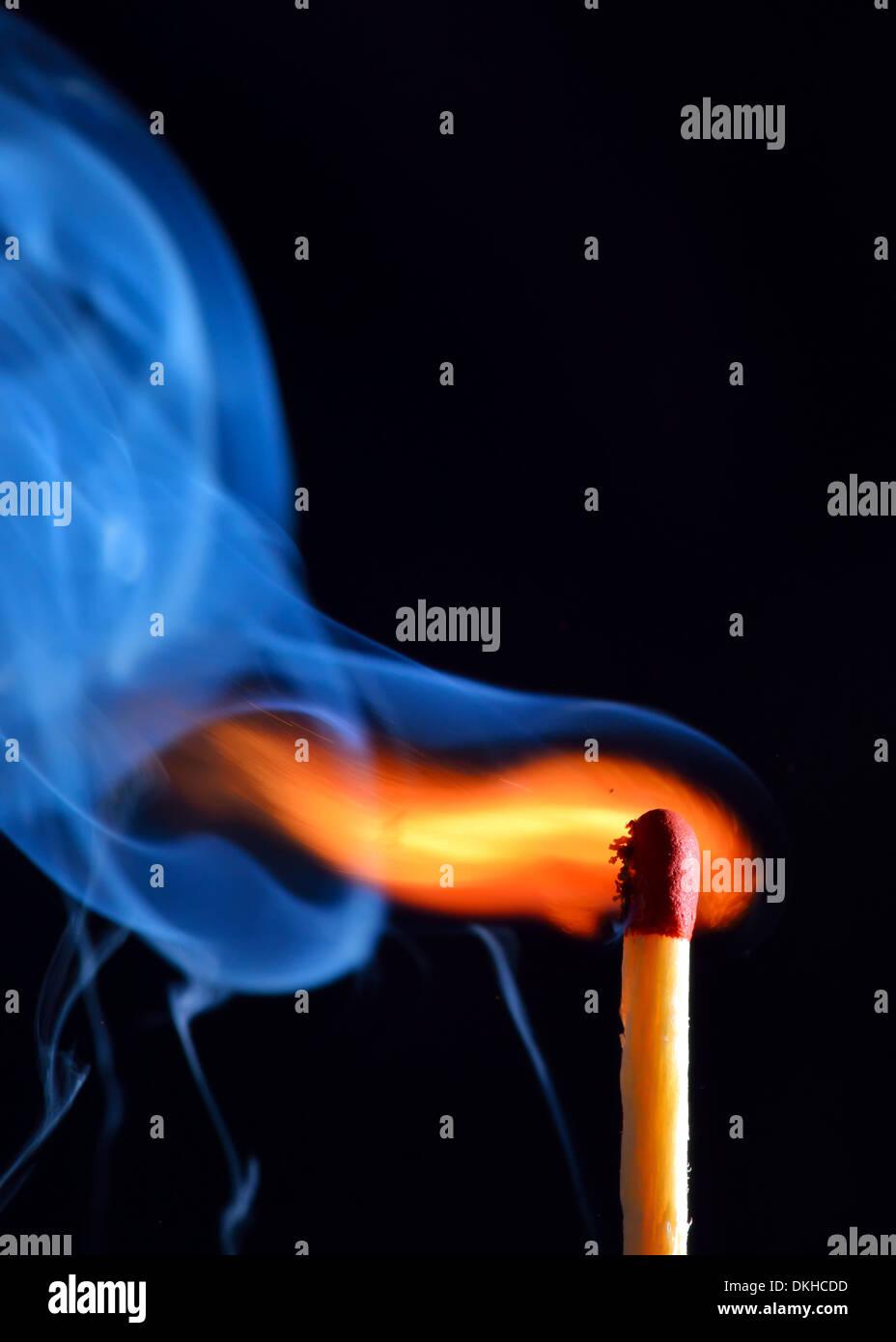 lighting a match on black background - Stock Image