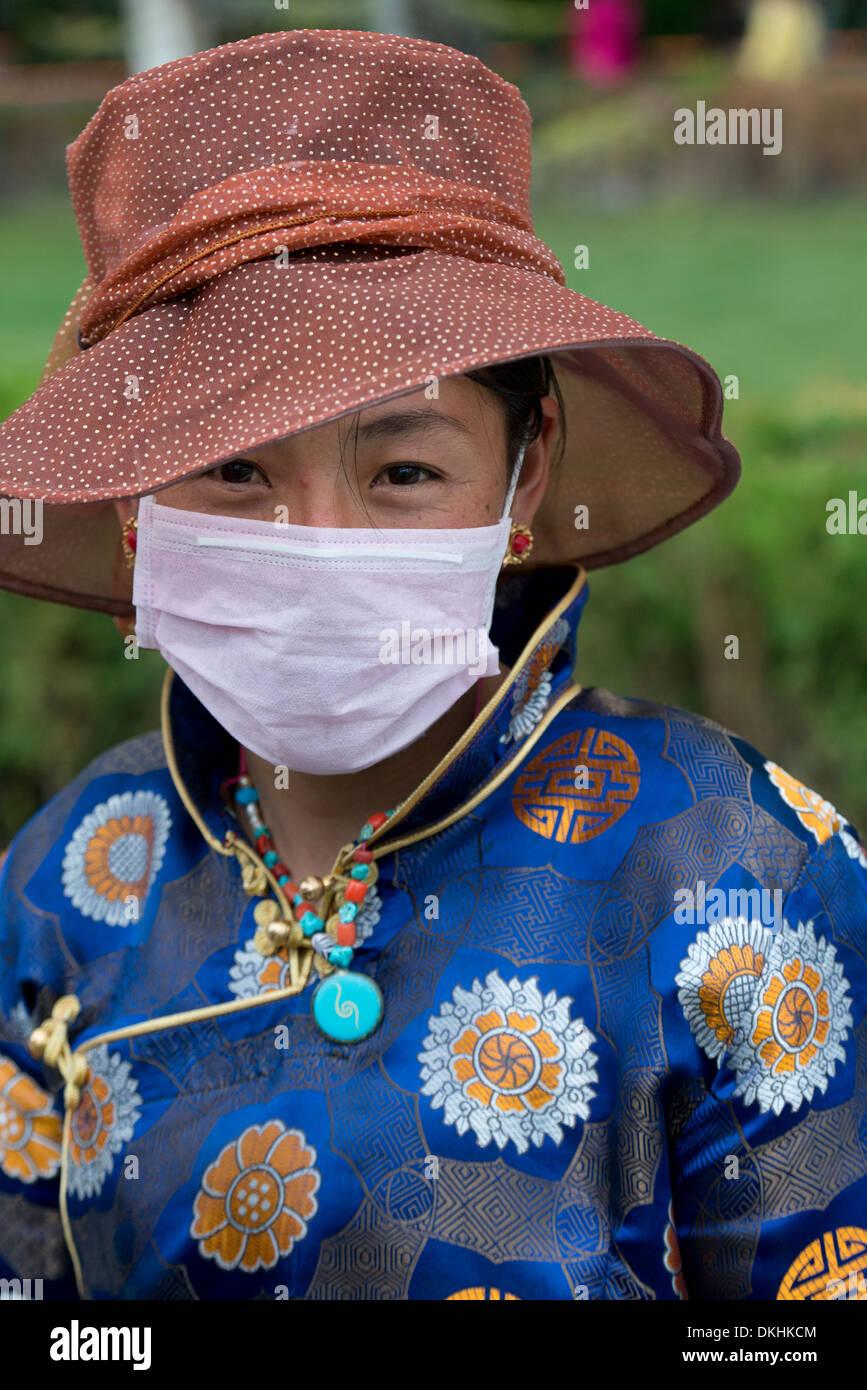 Portrait of Tibetan woman wearing pollution mask, Lhasa, Tibet, China - Stock Image