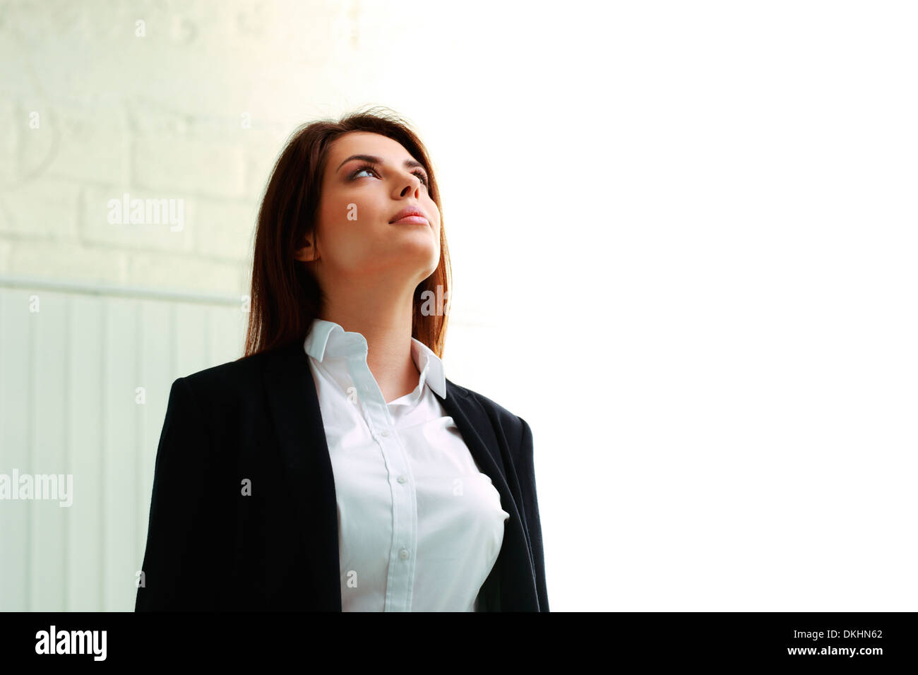 Young businesswoman looking up at copyspace in office - Stock Image