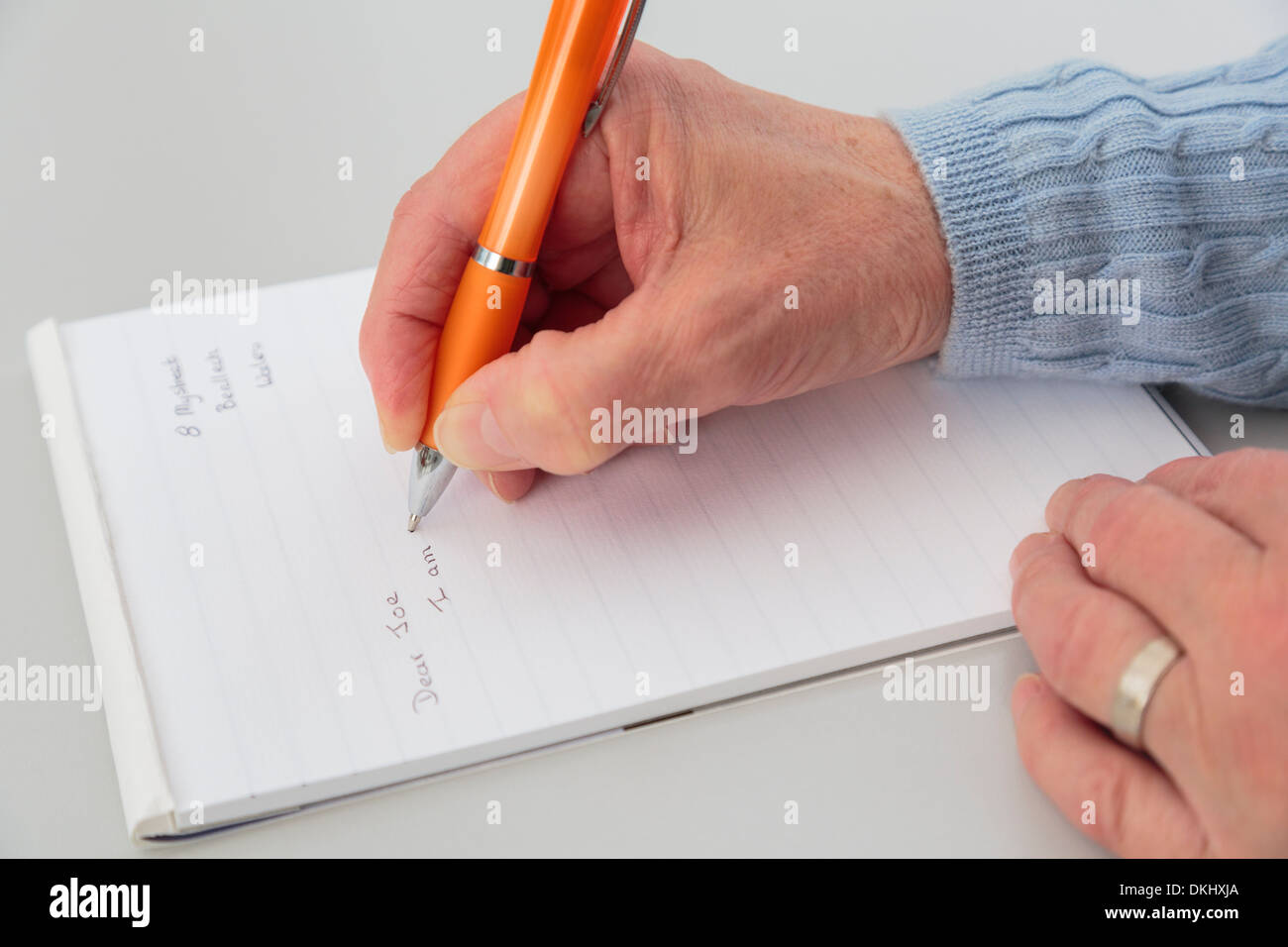 Top down of a right-handed senior woman's hand holding a pen writing a letter on a notepad of paper on a tabletop. Stock Photo
