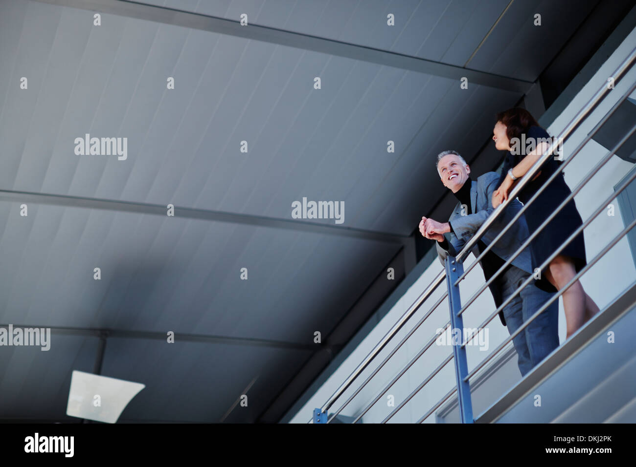 Business people talking at railing - Stock Image