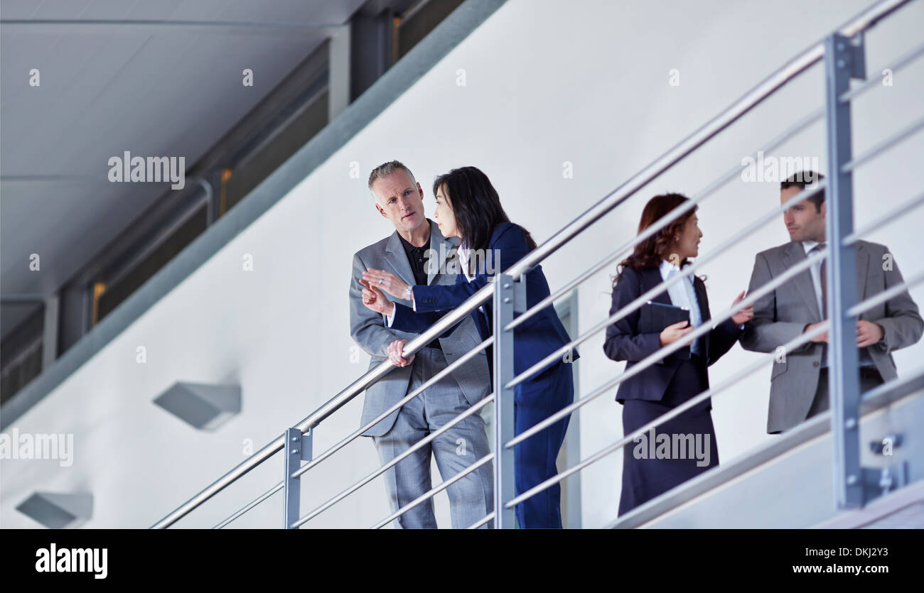Business people talking at railing n office - Stock Image