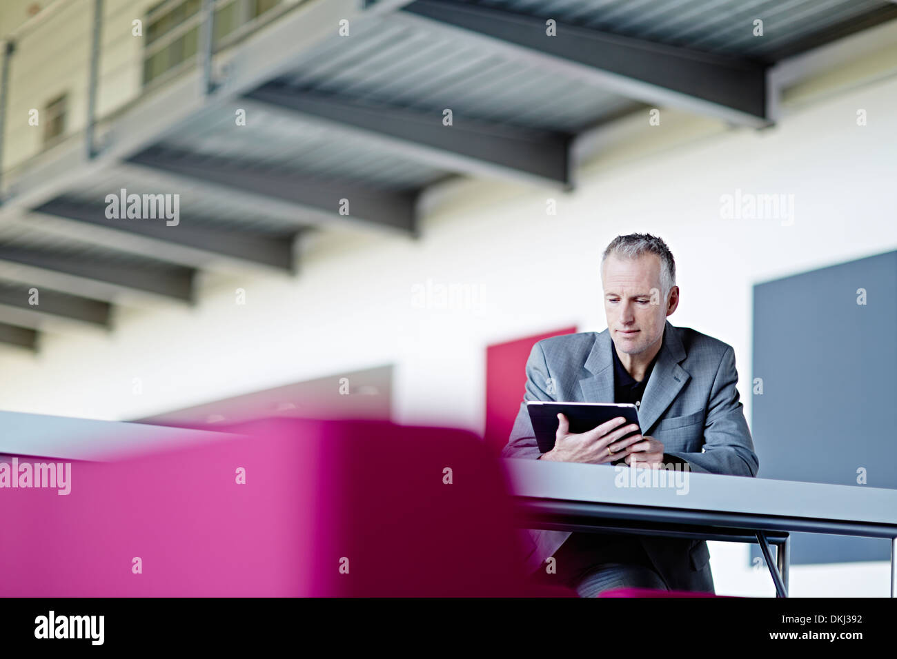 Businessman using digital tablet in lobby - Stock Image