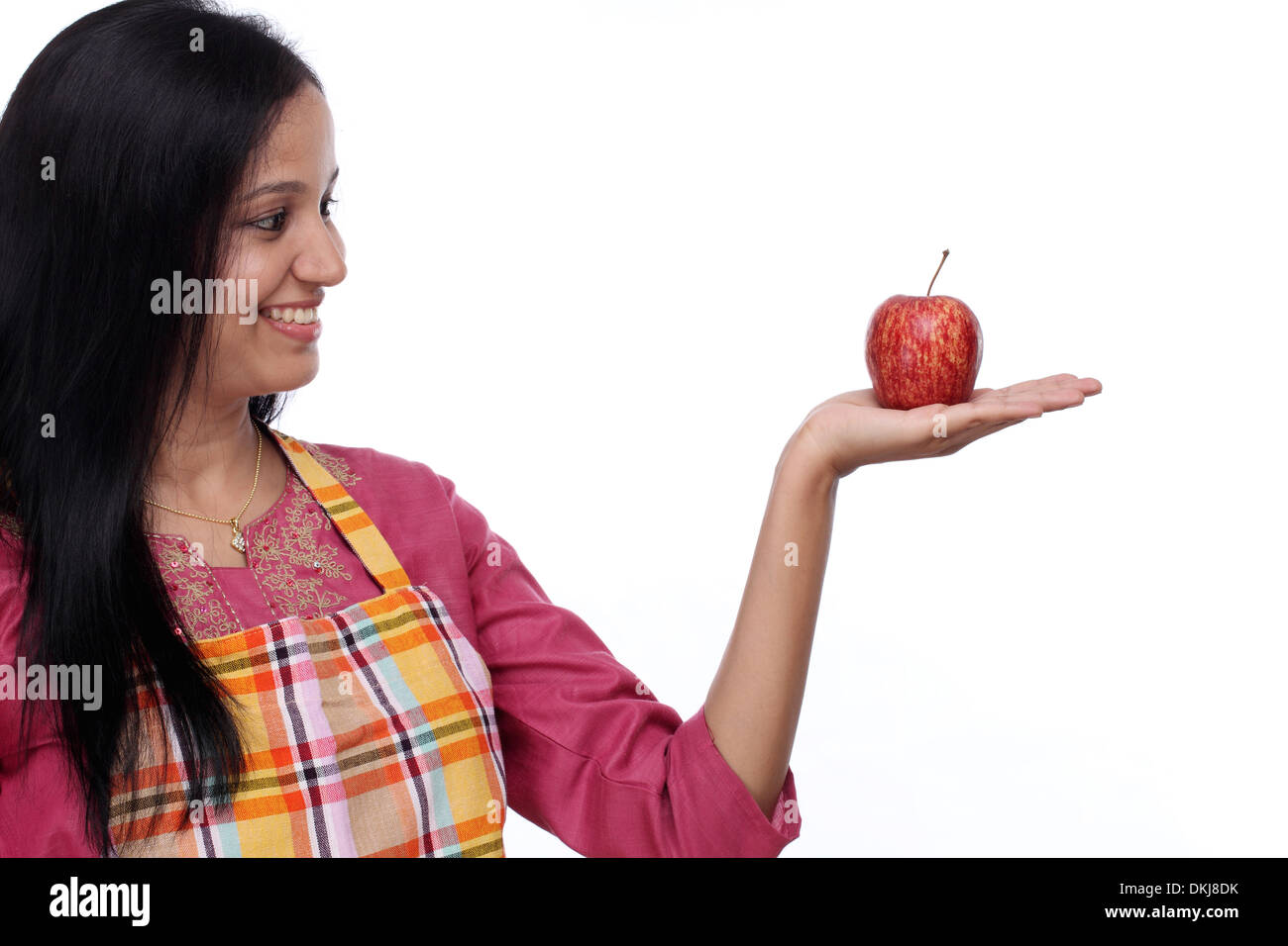 Happy young woman holding red apple against white background - Stock Image