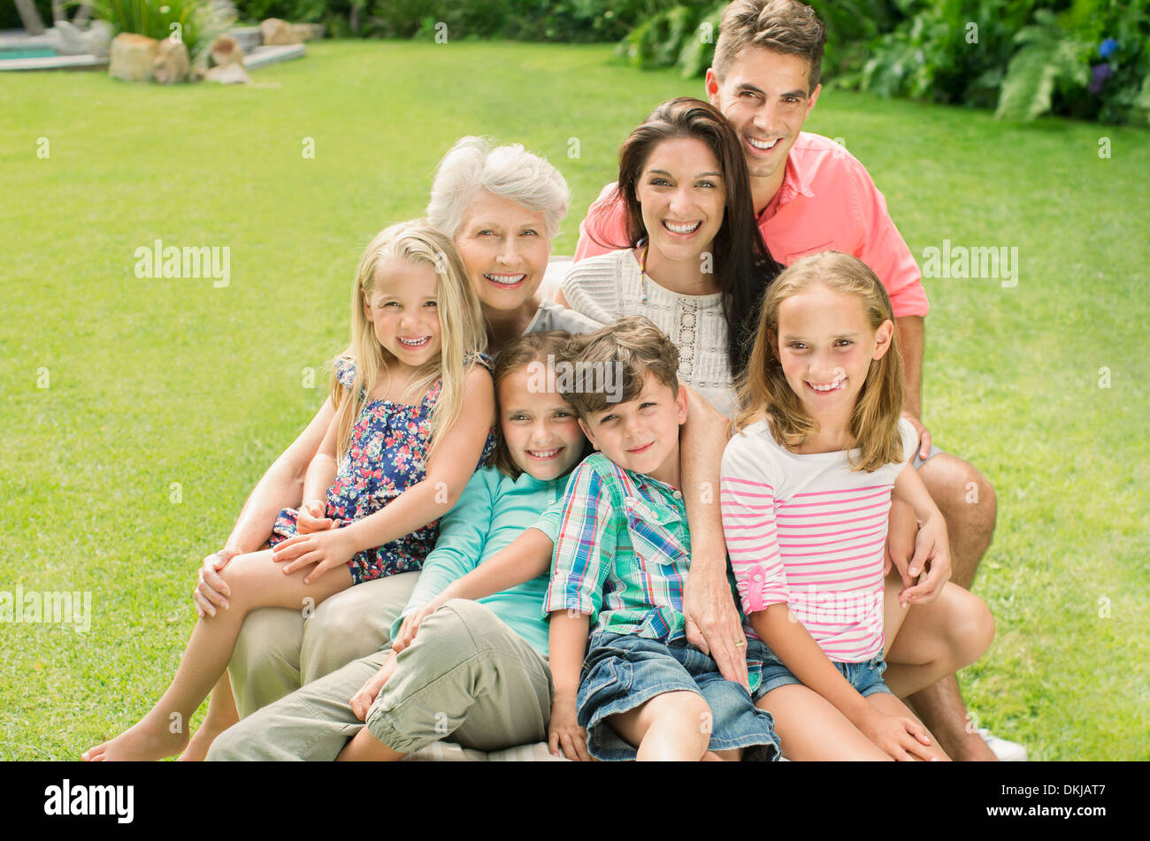 Multi-generation family smiling together in backyard Stock Photo