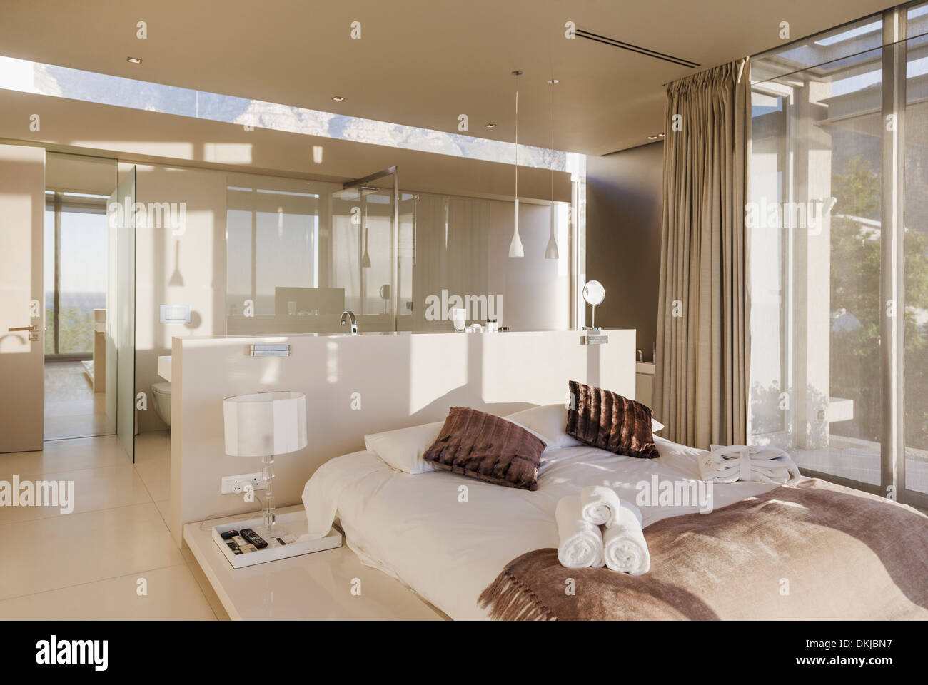 Bed and bathroom in modern master bedroom Stock Photo ...