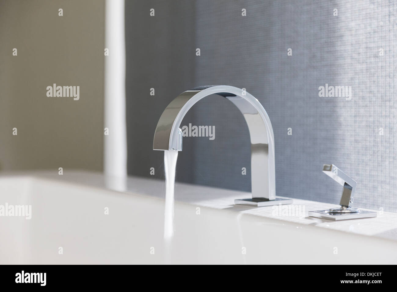 Water emitting from modern faucet Stock Photo