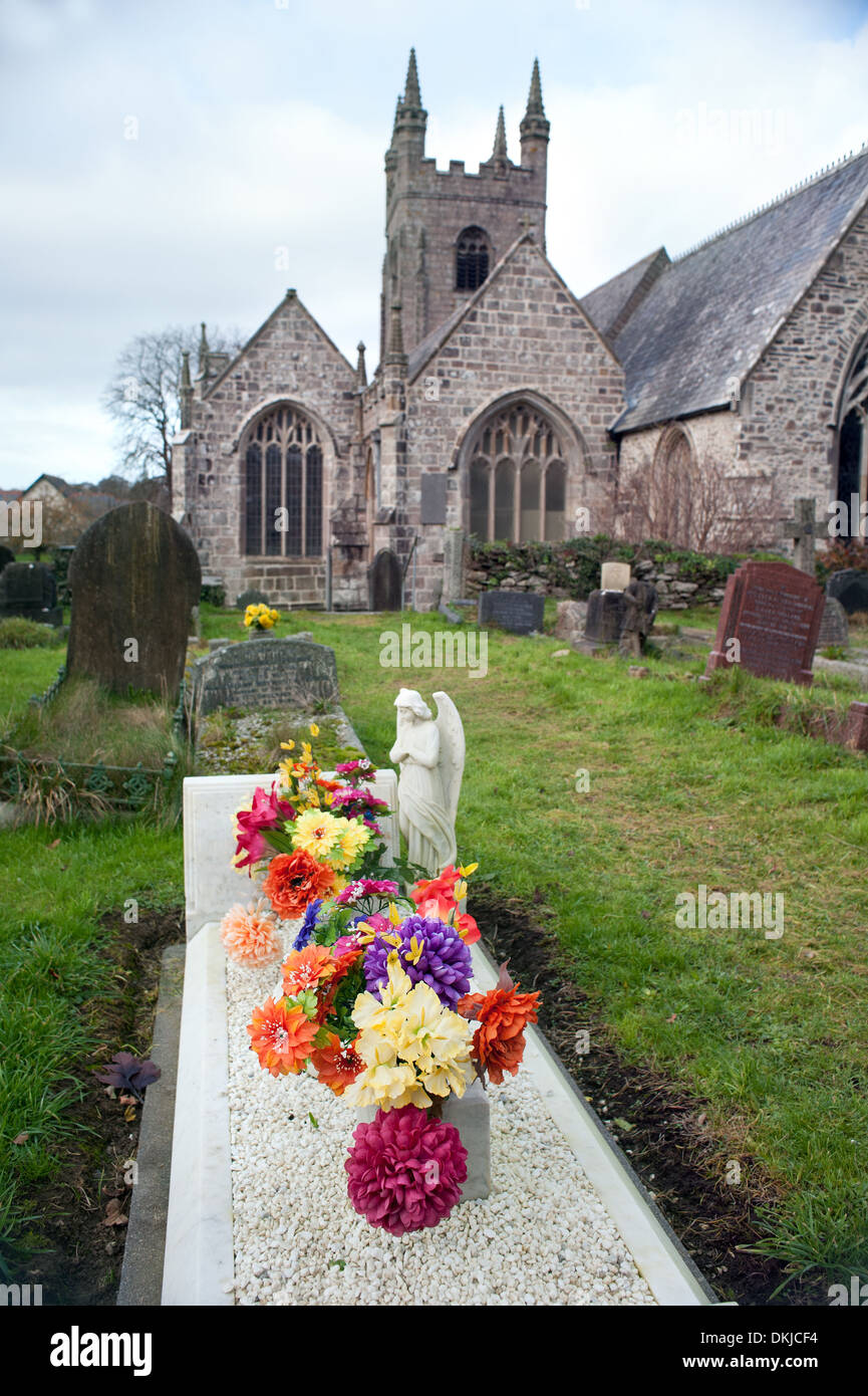 Fresh flowers are laid on this grave in a Devon church yard - Stock Image
