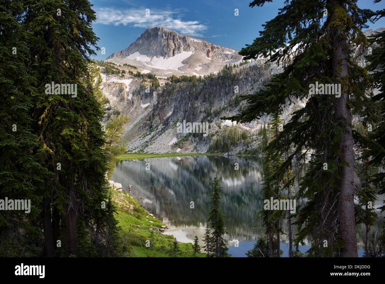 Fly fisherman and reflection in Mirror Lake with Eagle Cap Mountain. Eagle Cap Wilderness, Oregon - Stock Image