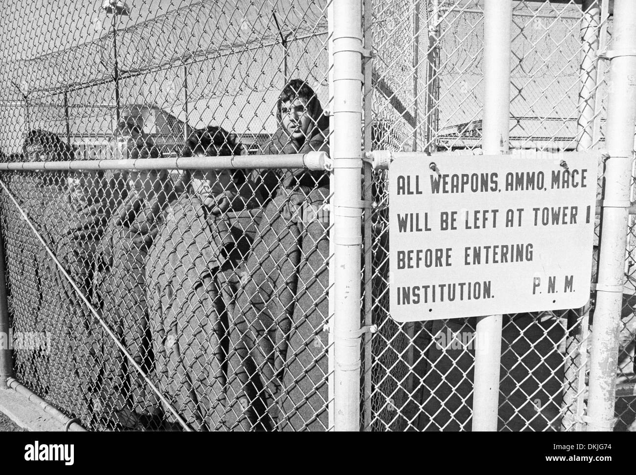 Inmates huddle in cold weather following the bloody 1980 riot at the New Mexico State Penitentiary - Stock Image