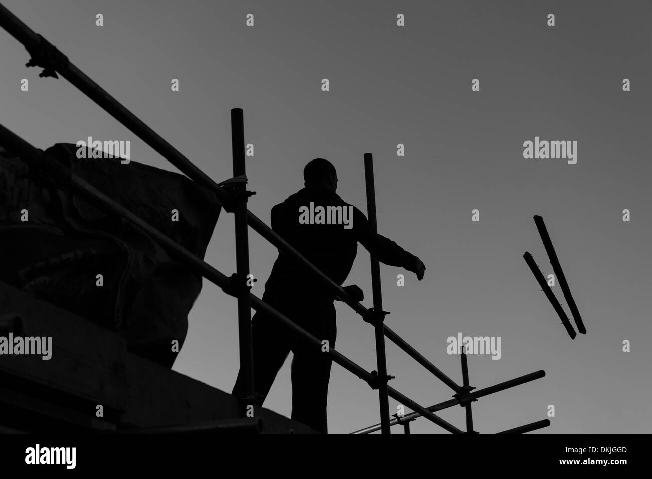 Silhouetted workman - a roofer - throwing two wooden planks off a scaffold. Home improvement renovation concept. - Stock Image
