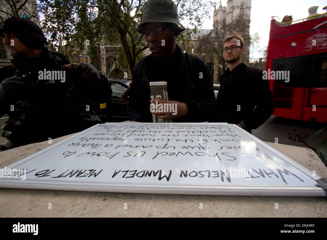 London UK. 6th December 2013. A  man  reads a tribute to former South Africa president Nelson Mandela 1918-2013 - Stock Image