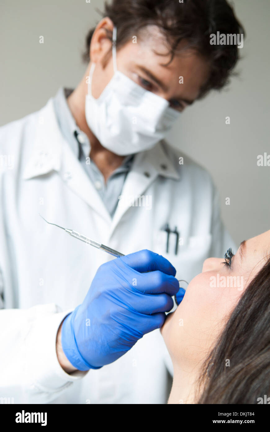 Male dentist wearing blue gloves examining smiling female dental patient - Stock Image
