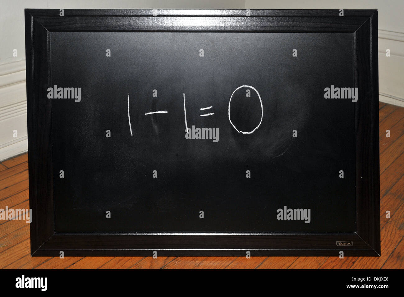 A blackboard with the sum 1-1=0 written on it in white chalk. - Stock Image