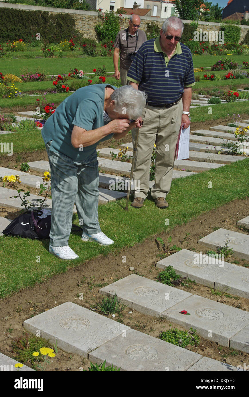 Senior lady taking a photo of a relative's grave in the WW1 cemetery of Boulogne East Stock Photo