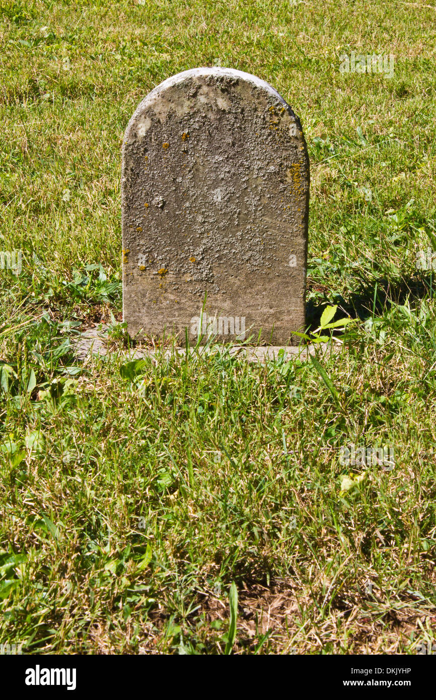 Small Unmarked Headstone - Small Unmarked Headstone in a Cemetery for a Child - Stock Image