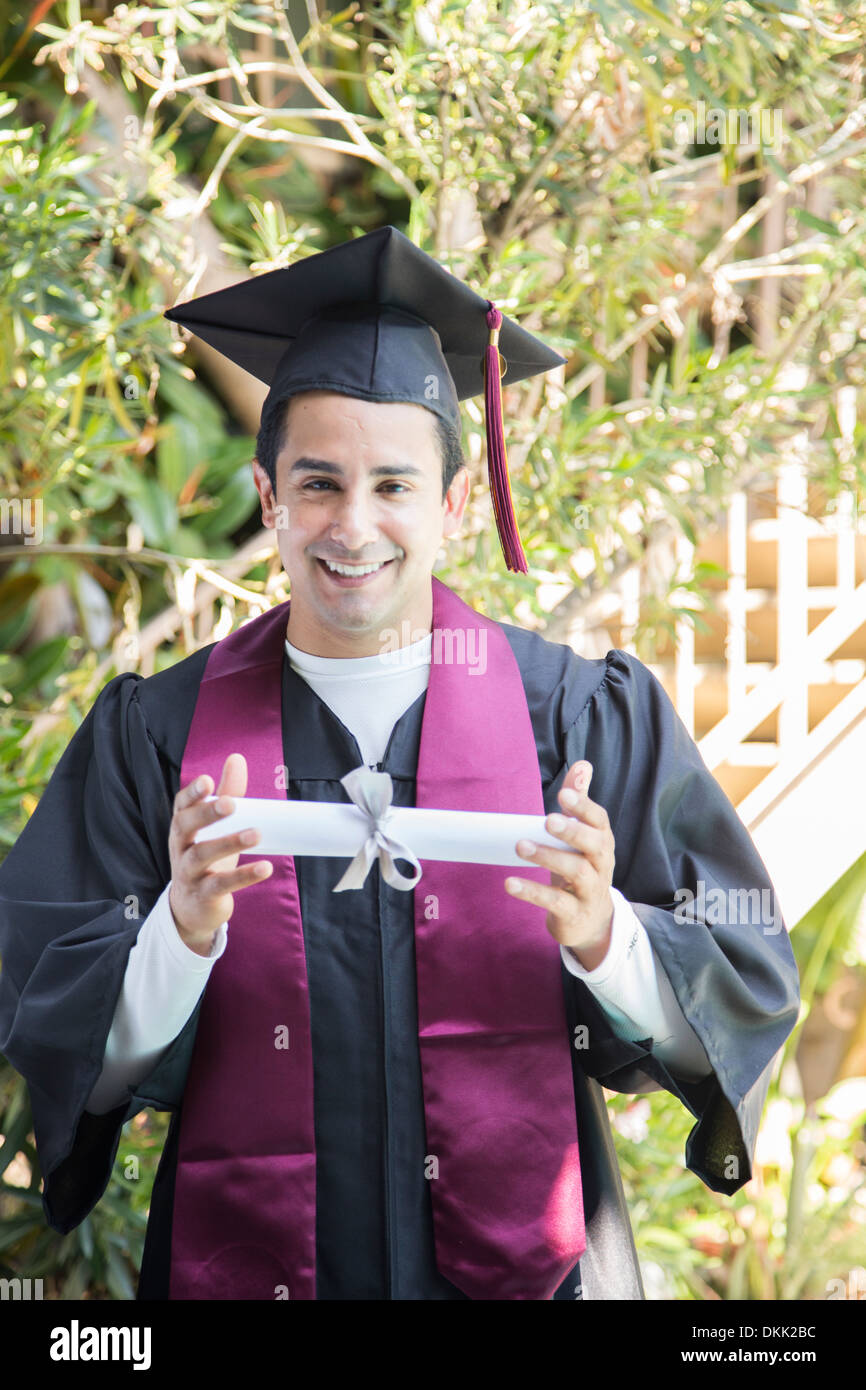 Smiling male graduate holding up diploma Stock Photo