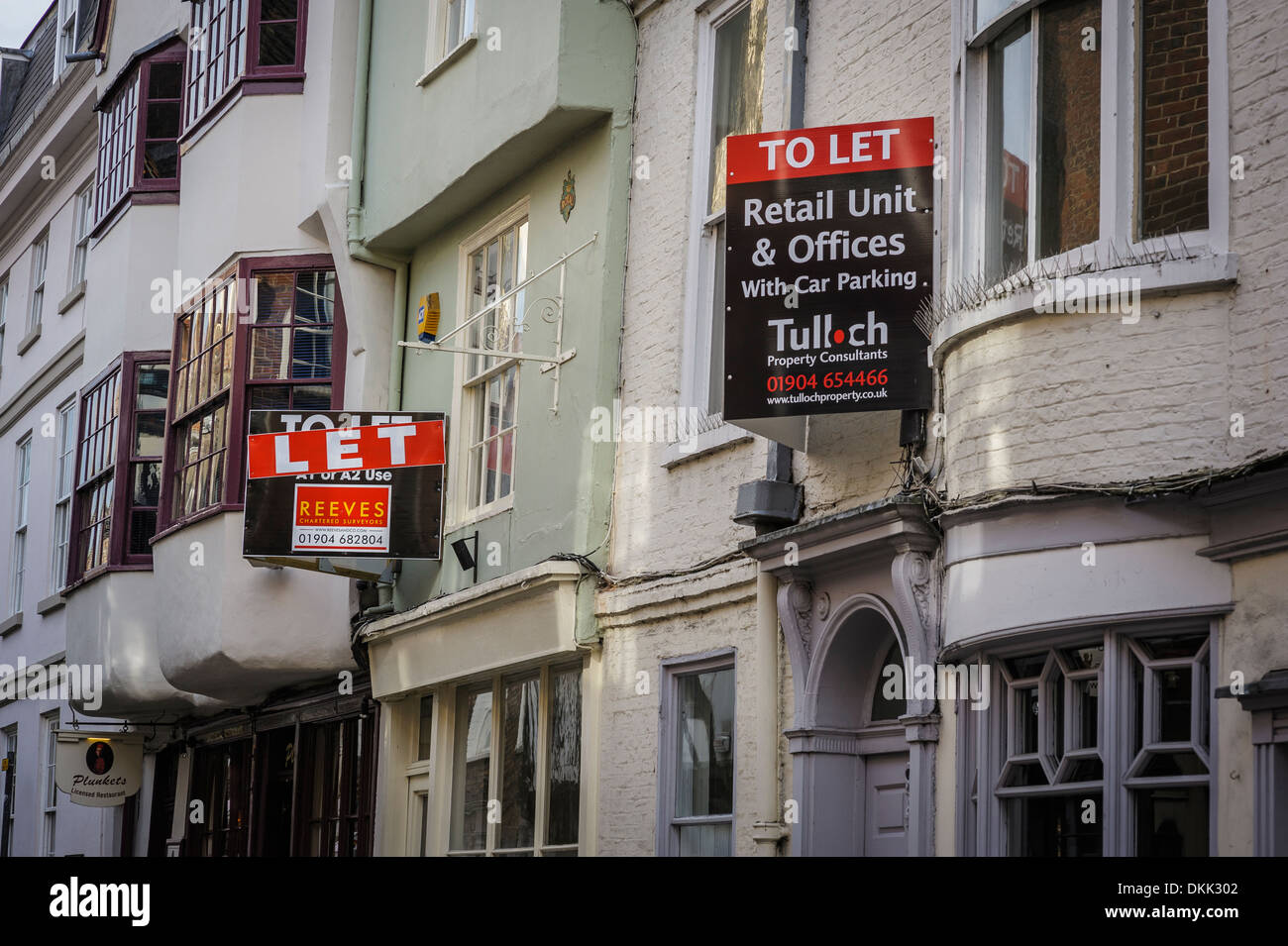 'To let' signs on old retail commercial buildings businesses down a York side street. A sign of the economic downturn recession - Stock Image