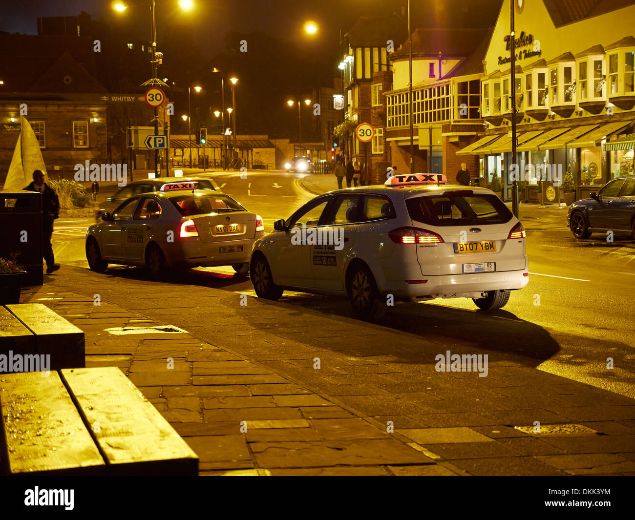 Taxis wait for late night fares in Whitby, Yorkshire - Stock Image