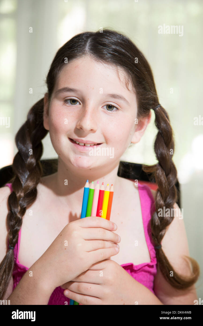 Young girl holding colored pencils - Stock Image
