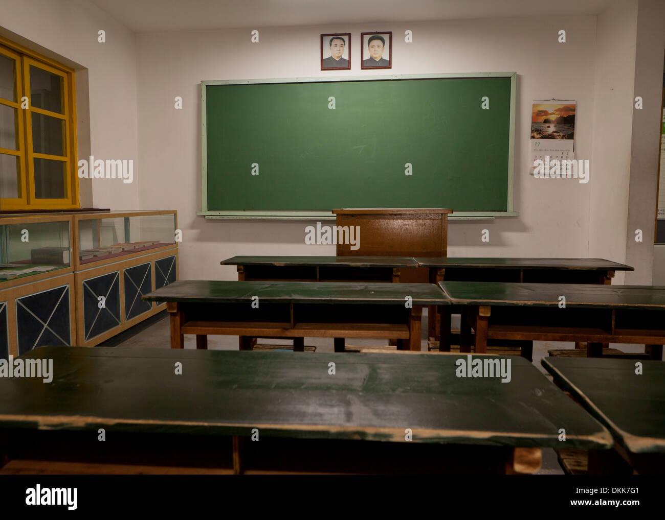 Mock-up of North Korean school classroom displaying portraits of Kim Il Sung and Kim Jong Il above blackboard - Stock Image