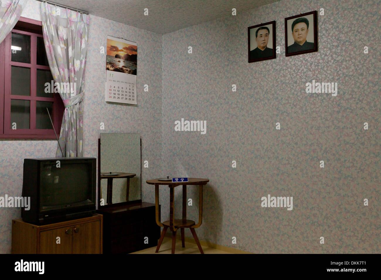 Mock-up of North Korean family home interior displaying portraits of Kim Il Song and Kim Jong Il on wall - Stock Image