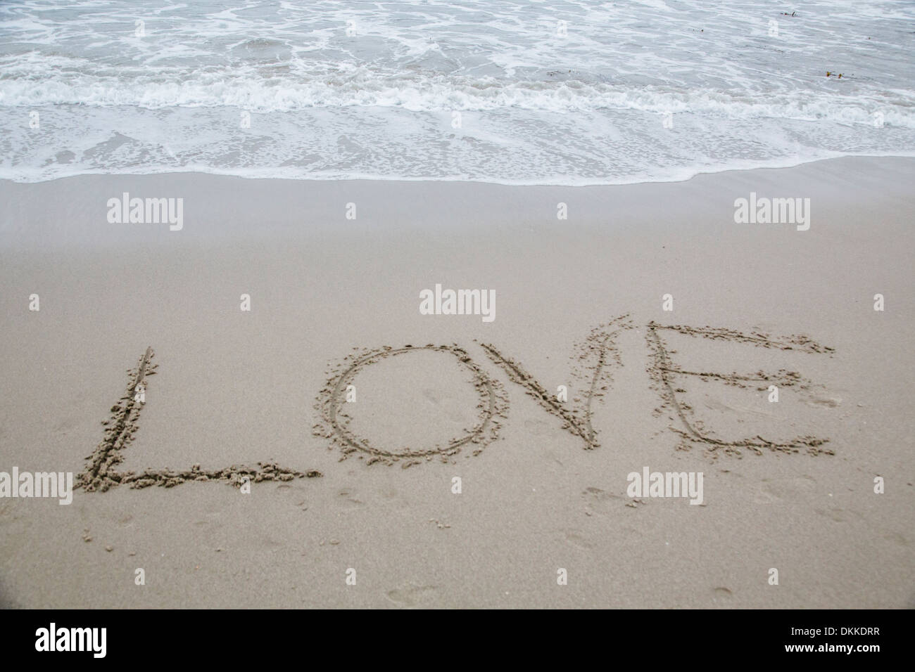 'Love' written in wet sand - Stock Image