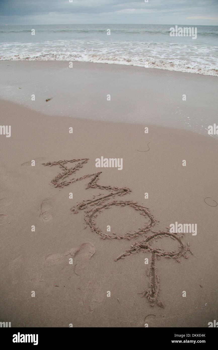 'Amor' written in wet sand - Stock Image