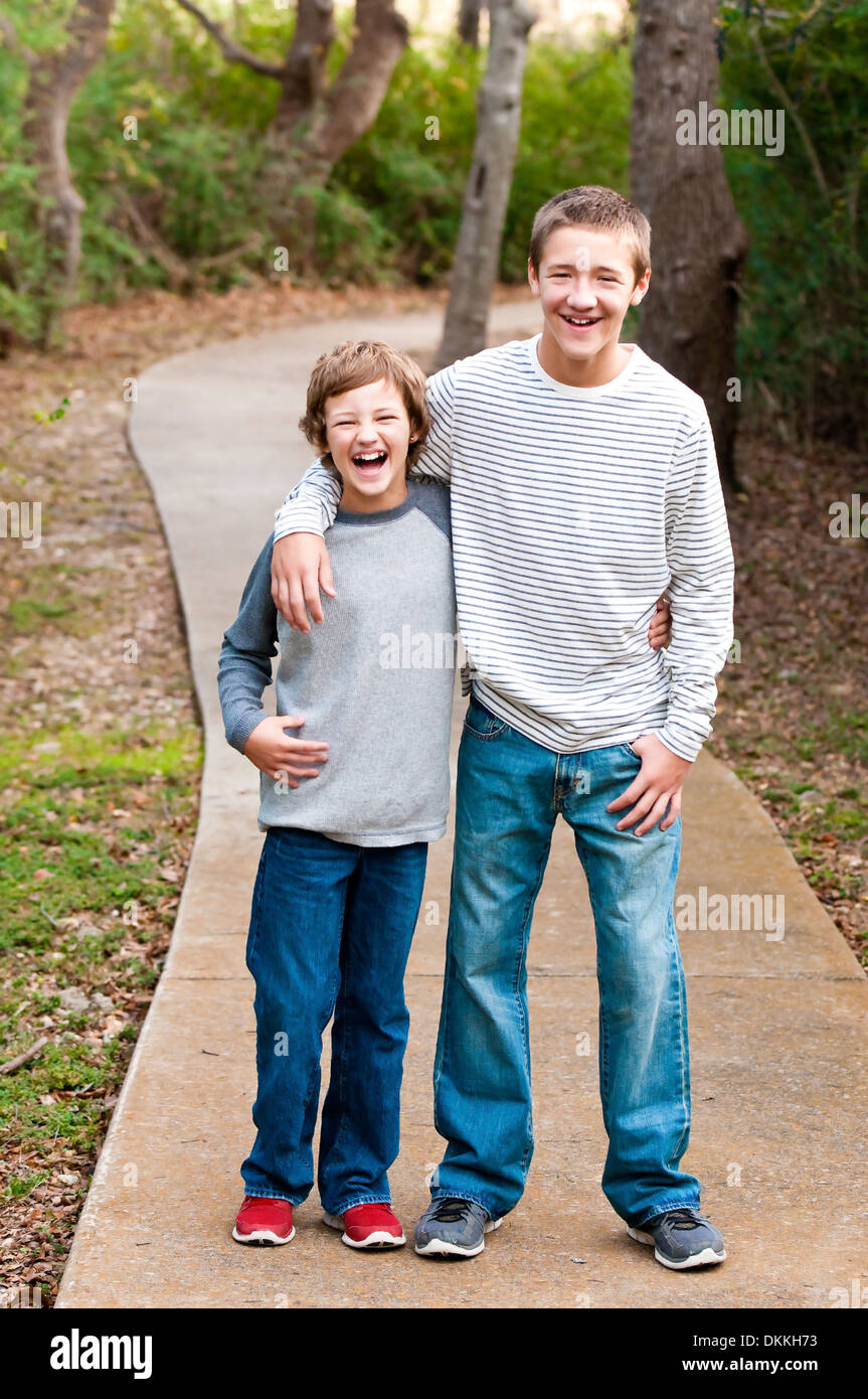 Cute happy teen brothers laughing outdoors. - Stock Image