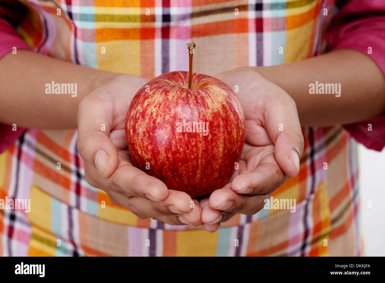Red apple in woman hands - Stock Image