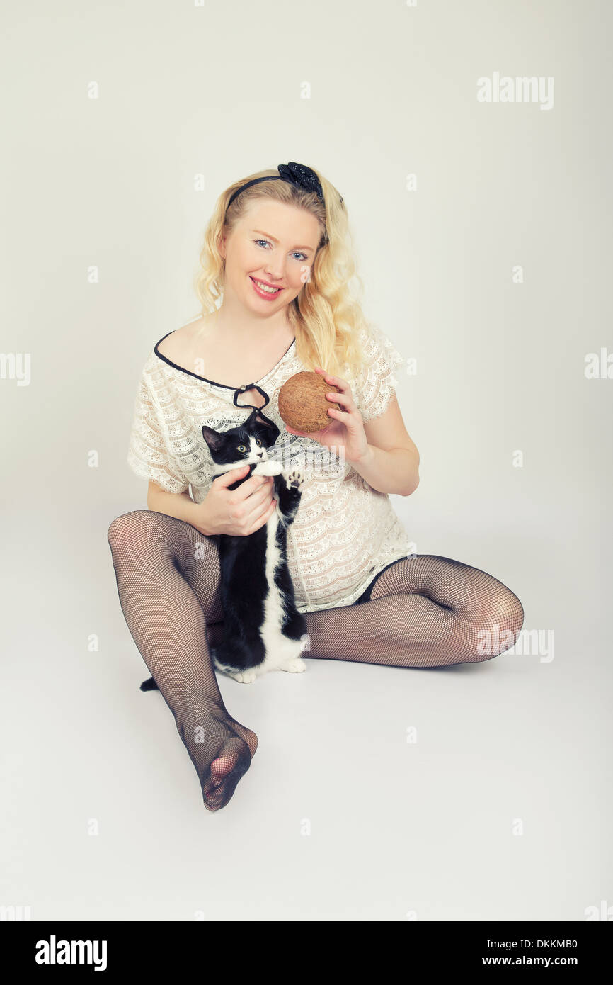 Pregnant Woman Plays with Cat and Coconut - Stock Image