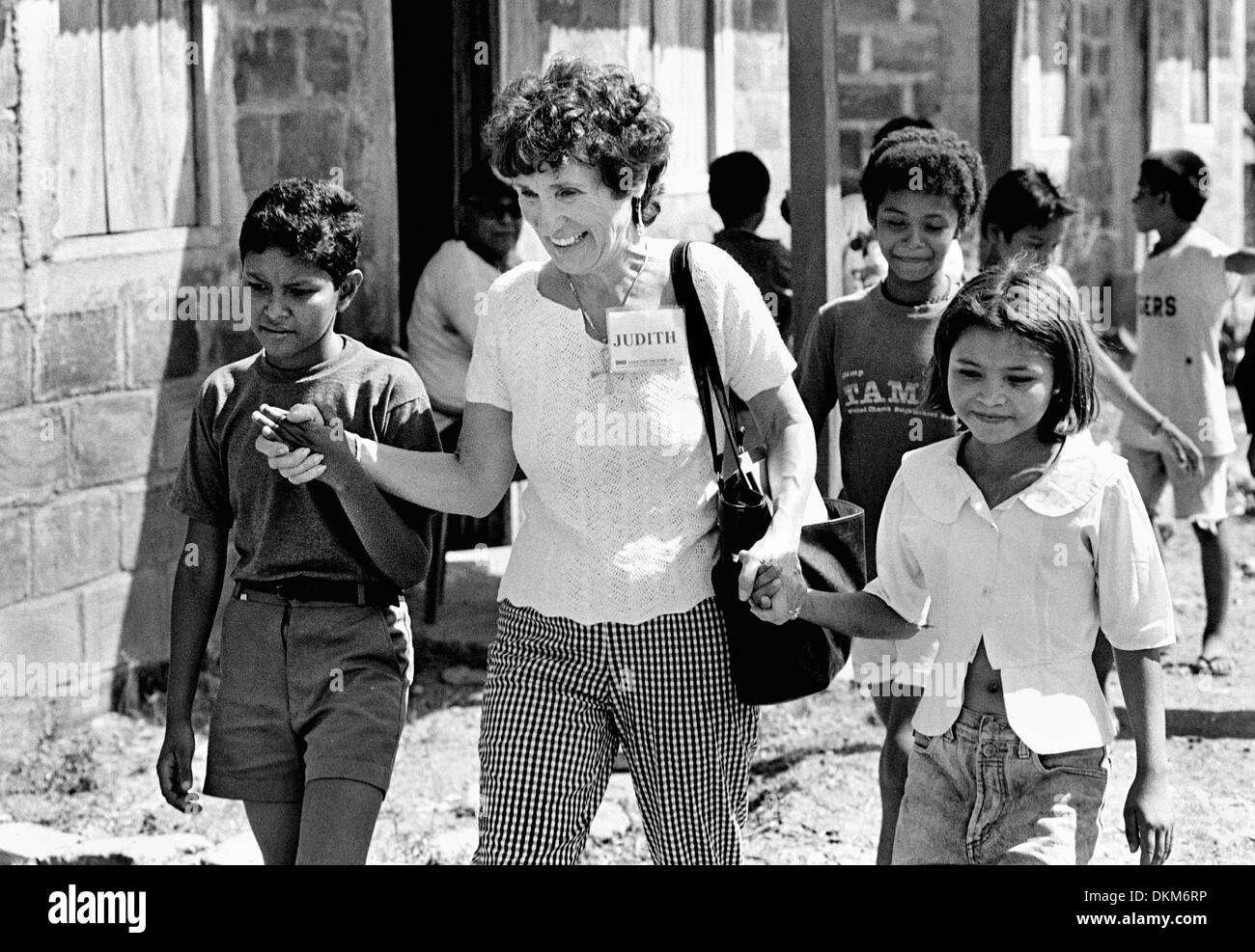 Nov. 19, 2002 - Chinandega, Nicaragua - Judith Sandman, of Wisconsin, walks hand in hand with children at the Villanueva housing project in Chinandega, Nicaragua, as they proudly give her a tour of their new homes. Amid scenes of desolation, the project, funded by Food For The Poor, Inc., gives pilgrims a hopeful glimpse of what can be accomplished to better the lives of the poor.  - Stock Image