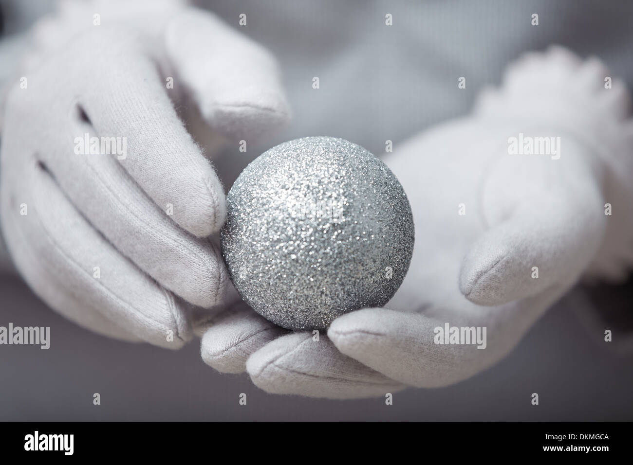 Human hands in warm mittens holding Christmas ball - Stock Image