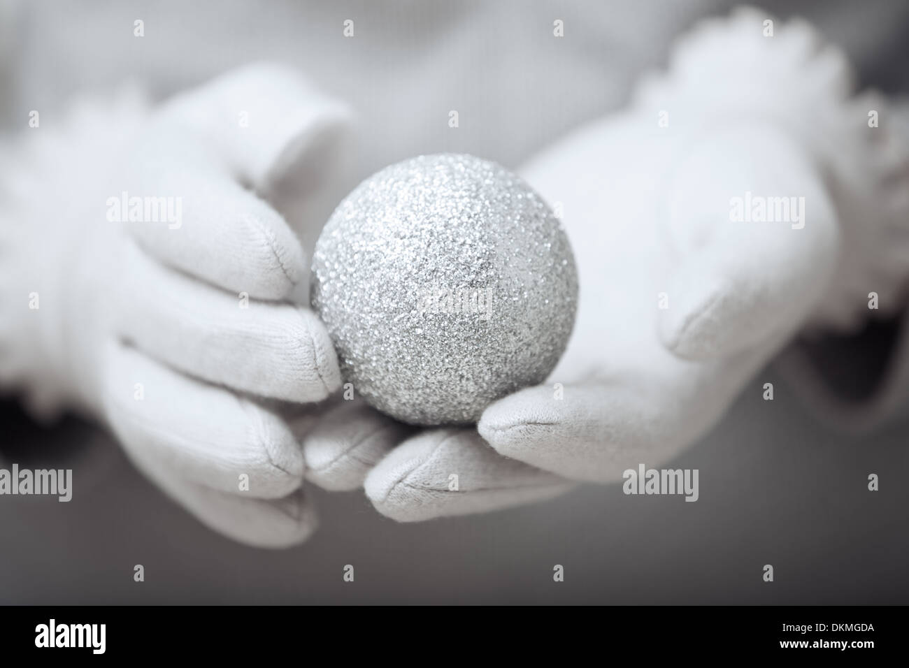 Human hands in mitten holding Christmas ball - Stock Image