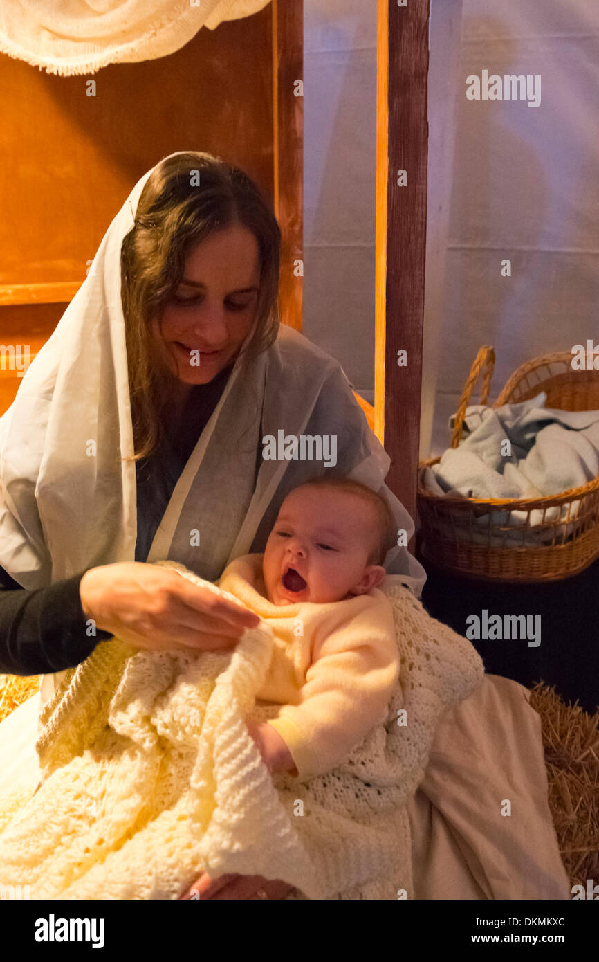 Garden City, New York, USA. December 6, 2013. Visitors experience the nativity scene at the manger, including Mary Stock Photo