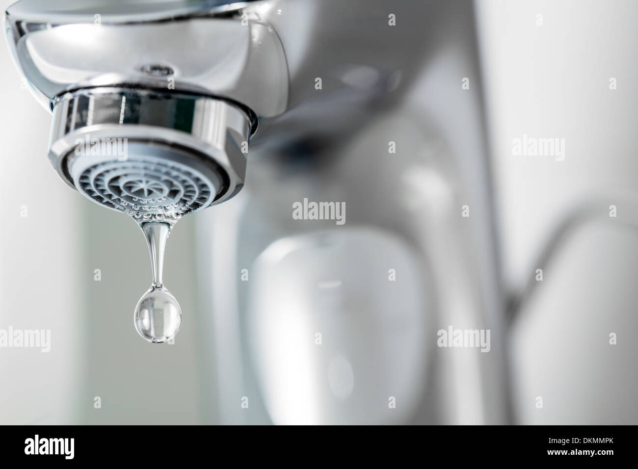 Tap closeup with dripping waterdrop. Water leaking, saving concept ...