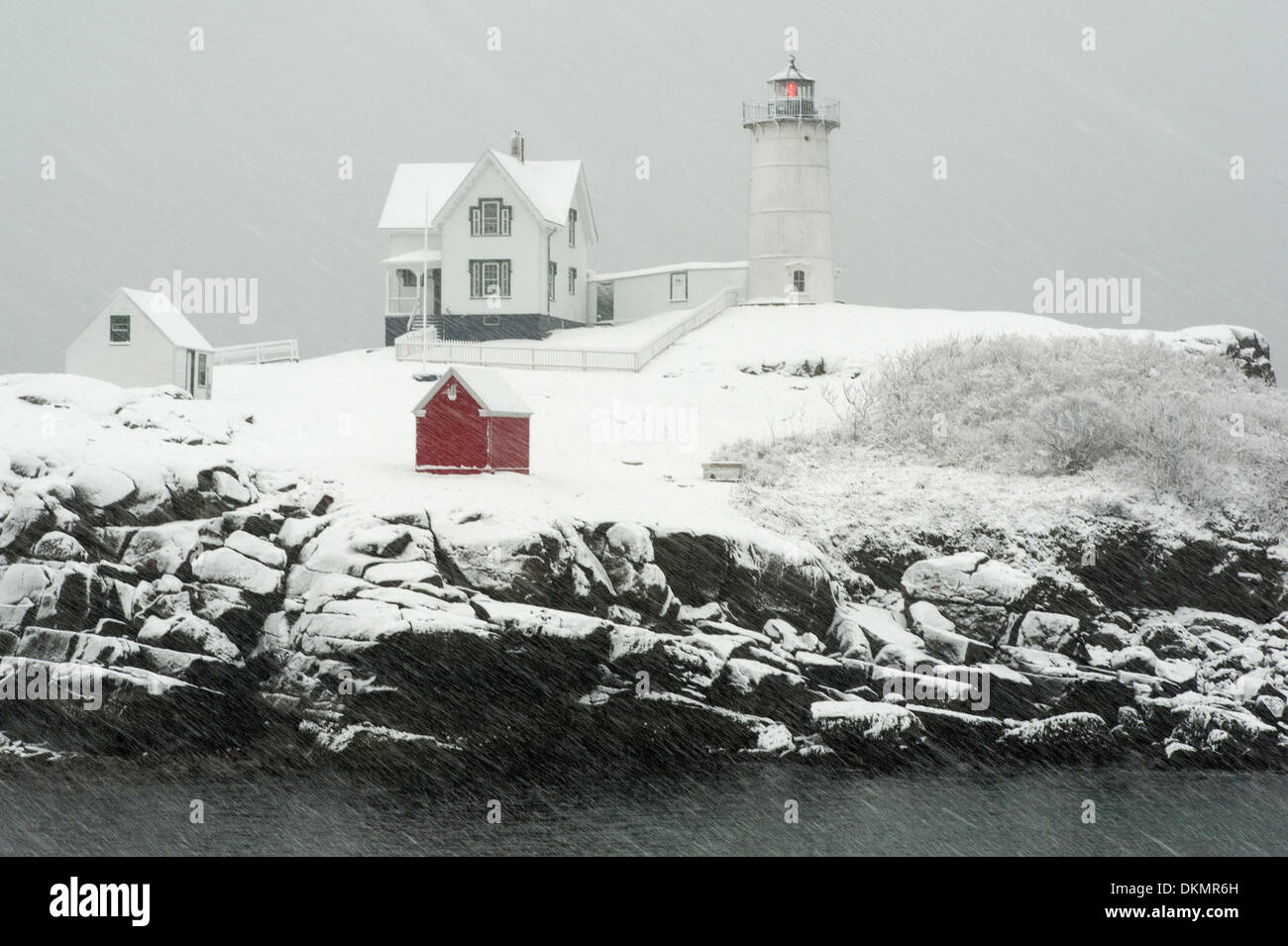 Nubble (Cape Neddick) lighthouse flashes its red light during snowstorm in Maine. - Stock Image