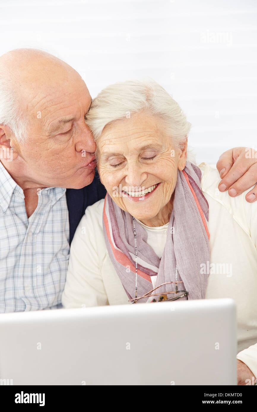 Happy man kissing smiling senior woman at computer - Stock Image