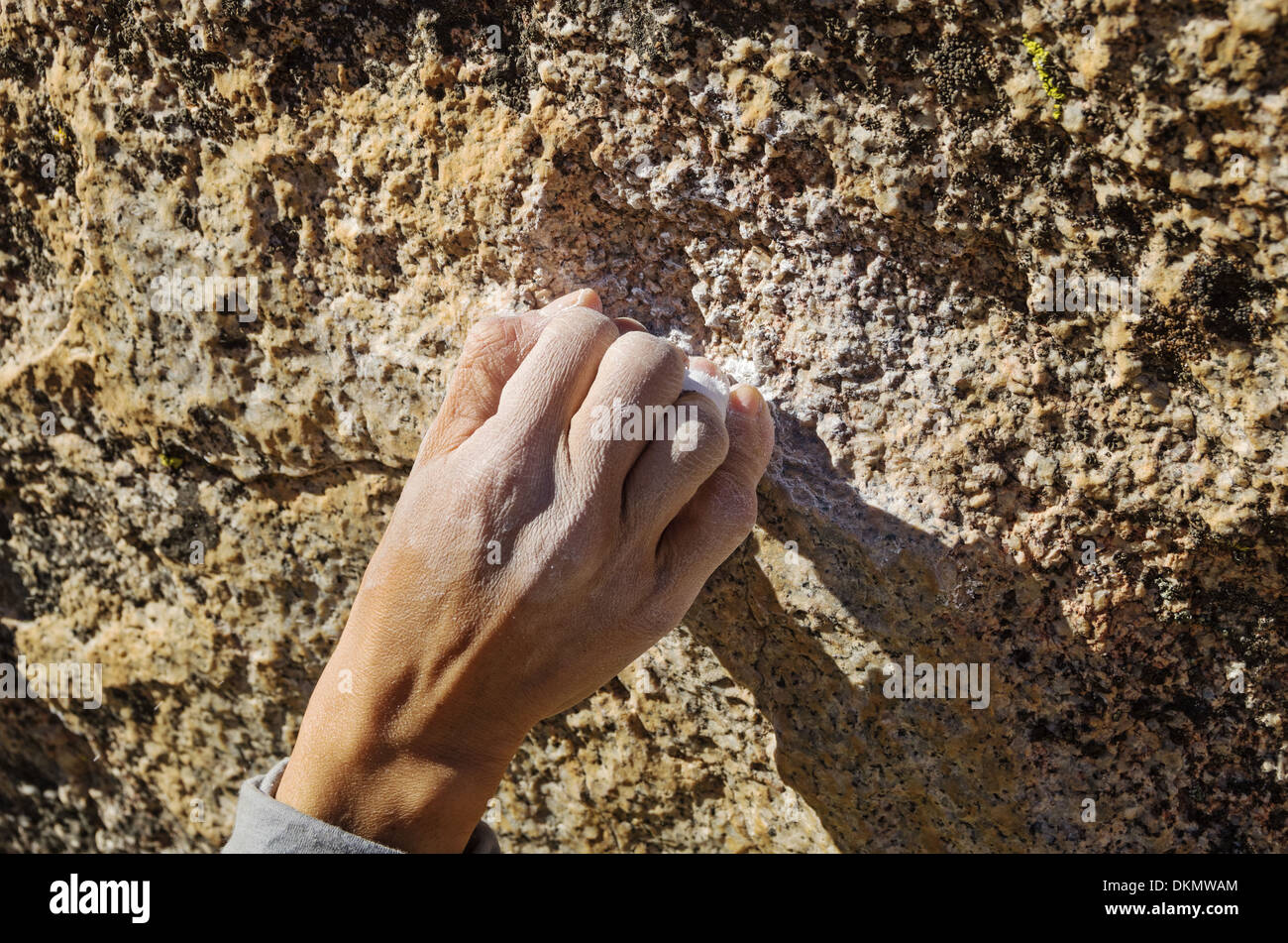 a woman climber hand grabbing a small rock hold with a crimp grip - Stock Image