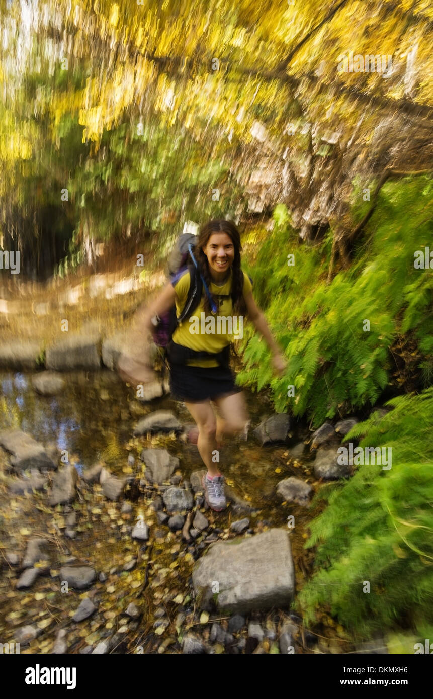 woman fast hiker crossing a stream with motion blur - Stock Image