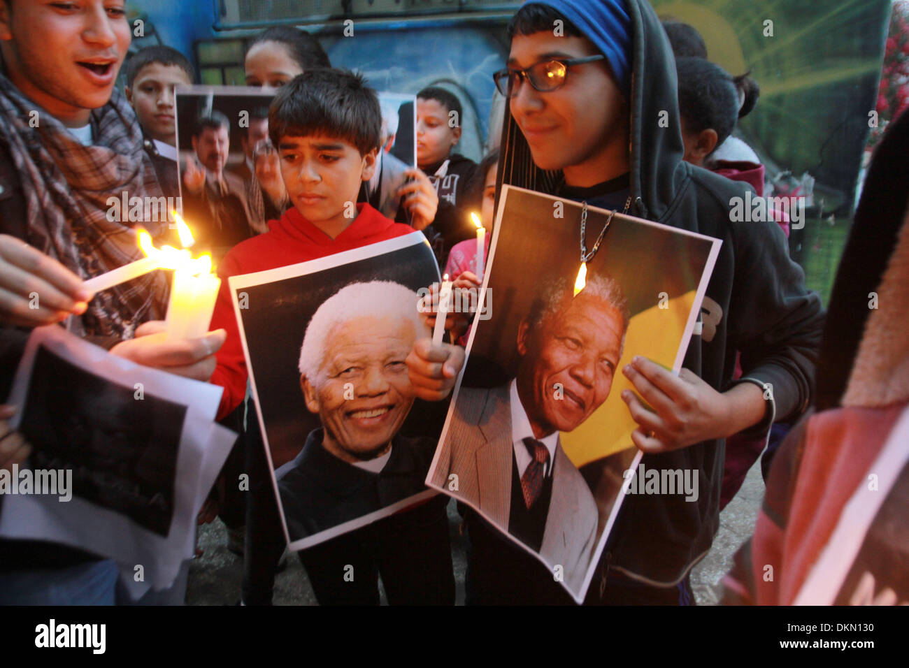 Nablus, West Bank, . 7th Dec, 2013. Palestinians light candles and hold pictures of former South African President Nelson Mandela in the West Bank refugee camp of Balata near Nablus. South African anti-apartheid hero Mandela died peacefully at home at the age of 95 on Thursday after months fighting a lung infection, leaving his nation and the world in mourning for a man revered as a moral giant. © Nedal Eshtayah/APA Images/ZUMAPRESS.com/Alamy Live News Credit:  ZUMA Press, Inc./Alamy Live News - Stock Image
