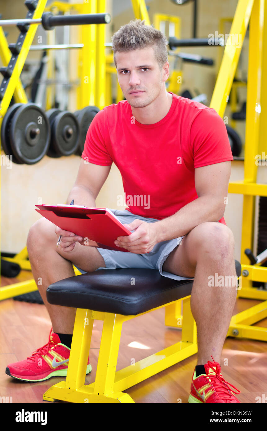 Young male personal trainer holding clipboard, sitting on training equipment in gym - Stock Image