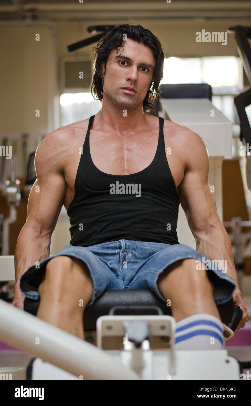Bodybuilder in gym working out on legs machine, looking at camera. - Stock Image