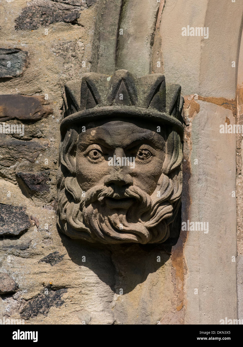 Small carved stone wall boss of bearded King's Head with Crown - Stock Image