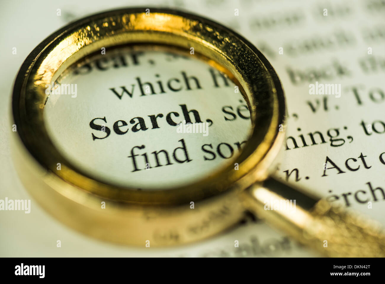 Macro Image Of A Magnifying Glass Over The Search Word In A Dictionary - Stock Image