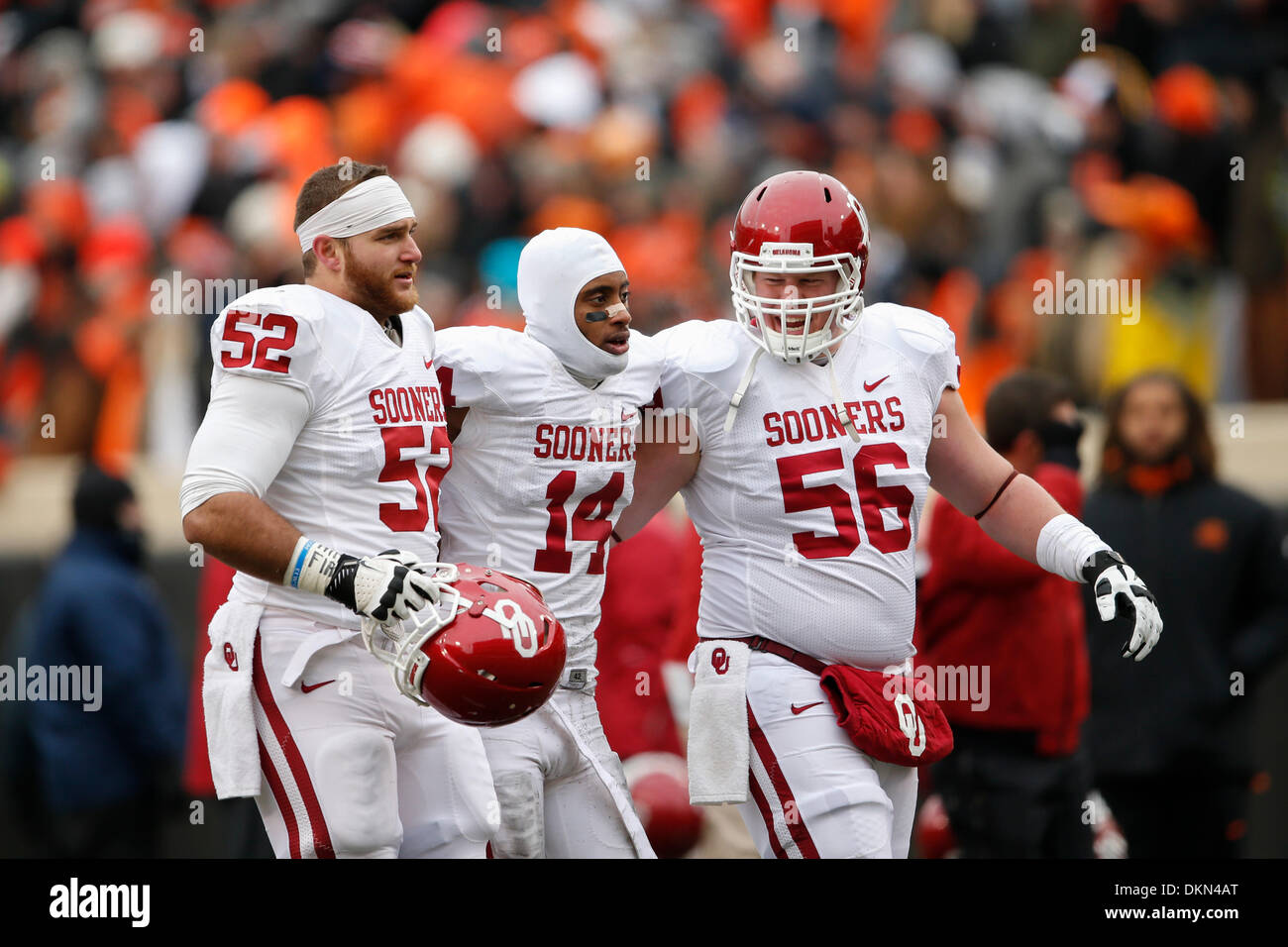 Stillwater, Oklahoma, USA. 7th Dec, 2013. December 7, 2103: Oklahoma Sooners offensive linesman John-Philip Hughes (52) and offensive linesman Ty Darlington (56) help defensive back Aaron Colvin (14) off the field after the NCAA football game between the Oklahoma Sooners and the Oklahoma State Cowboys at Boone Pickens Stadium in Stillwater, OK. The Sooners defeated the Cowboys 33-24. Credit:  csm/Alamy Live News - Stock Image
