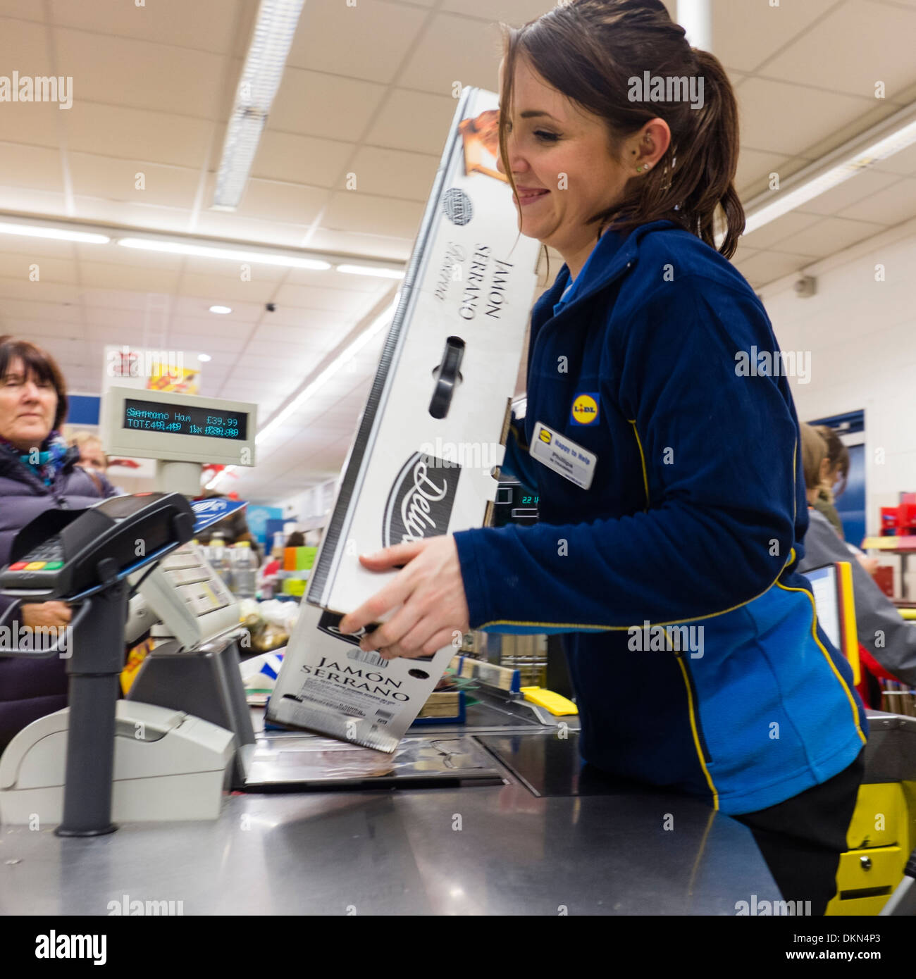 A check out woman scanning a whole Serrano ham, one of Lidl discount supermarket 'Deluxe' range of foods, UK - Stock Image