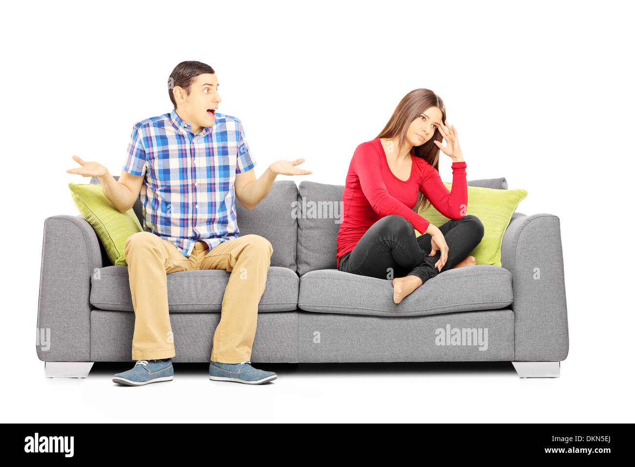 Young heterosexual couple sitting on a couch during an argument - Stock Image